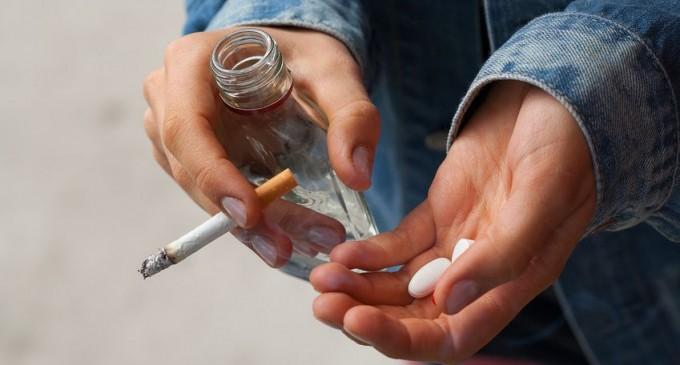 kobieta z papierosem, wódką i tabletkami