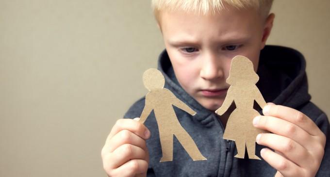 chłopiec trzymający wycięte postacie z papieru