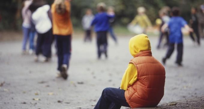 samotnie siedzące dziecko wśród innych dzieci