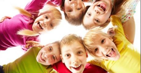 Śmiejące się dzieci obejmujące się tworzące koło