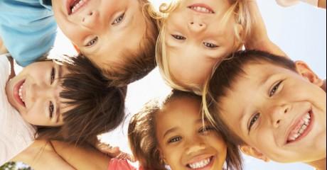 Dzieci obejmujące się tworzą koło i uśmiechają się